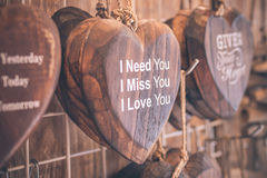 Houten die harten keurig op een turkooise uitstekende houten achtergrond worden geplaatst Handcrafted houten harten met tekst in  Royalty-vrije Stock Foto's
