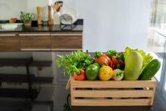 Houten die kratten met diverse soorten verse die groenten worden gevuld op de teller in de keuken worden geplaatst stock foto's