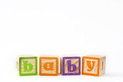 Houten die kubussen met brieven met `-baby` woord op witte achtergrond wordt geïsoleerd Stock Foto