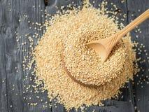 Houten die lepel van licht hout in een houten komhoogtepunt wordt gemaakt van quinoa zaden op een donkere lijst De mening vanaf d stock afbeeldingen
