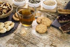 Houten die lijst voor een zoet veganistontbijt wordt geplaatst met thee, gesneden banaan, gemengd gedroogd fruit, veganistkoekjes stock fotografie