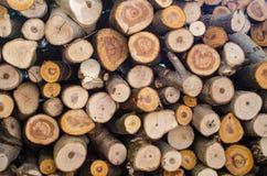 Houten die logboeken in een stapel worden en op de komende winter worden voorbereid gegroepeerd die stock foto