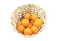 Houten die mand met sinaasappelen wordt gevuld Stock Afbeeldingen