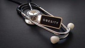 Houten die markering met ZWAARLIJVIGHEID en stethoscoop op zwarte achtergrond wordt geschreven Medisch en gezondheidszorgconcept Stock Afbeelding