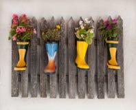 Houten die omheining decoratet met bloemen in rubberlaarzen worden geplant royalty-vrije stock fotografie