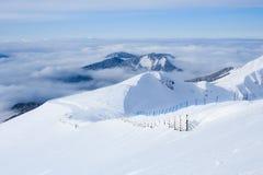 Houten die omheining en skisleep in de bergen van de Kaukasus met sneeuw worden behandeld Royalty-vrije Stock Afbeeldingen