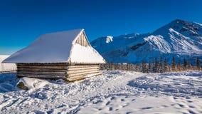 Houten die plattelandshuisje met sneeuw in de bergen wordt behandeld Stock Foto