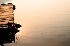 Houten die ponton met reddingsboei wordt omringd die op rimpelingswaterspiegel met weerspiegeling van zonlicht tijdens zonsopgang stock fotografie