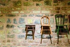 Houten die stoel voor een bakstenen muur wordt geplaatst Royalty-vrije Stock Afbeeldingen