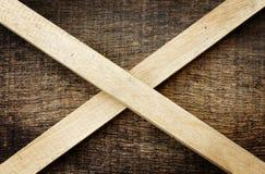 Houten die stokken op oude houten worden gekruist Stock Afbeeldingen