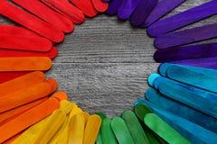 Houten die stokken in verschillende kleuren op een houten lijst worden geschilderd Stock Afbeelding