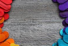 Houten die stokken in verschillende kleuren op een houten lijst worden geschilderd Stock Afbeeldingen