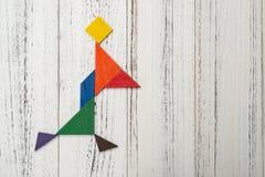 Houten die tangram als snel lopend meisje wordt gevormd stock fotografie