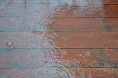 Houten die terras door regen wordt overstroomd Stock Foto's