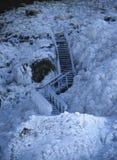 Houten die trap in ijs wordt bevroren, met ijskegels tegen een bevroren die lavagebied wordt behandeld met ijs en sneeuw wordt be royalty-vrije stock foto