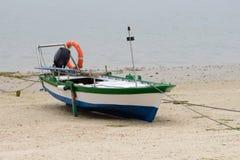 Houten die vissersboot op de kust wordt vastgelegd stock foto's