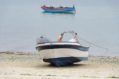 Houten die vissersboot op de kust wordt vastgelegd stock fotografie