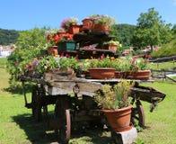 houten die wagen met vele potten van bloemen wordt verfraaid Stock Foto's