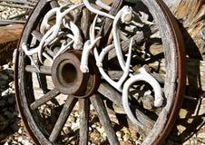Houten die wagenwiel met hertengeweitakken wordt verfraaid stock afbeeldingen