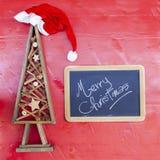 Houten diy Kerstmisboom en bord over een rode achtergrond stock foto