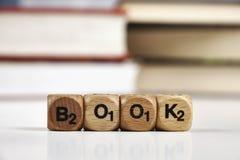 Houten dobbel met het woordenboek met vage boeken stock afbeeldingen