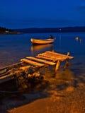 Houten dok en boot bij nacht stock afbeeldingen