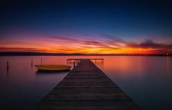 Houten Dok en vissersboot bij het meer, zonsondergangschot stock afbeeldingen