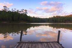 Houten dok op rustig meer met zonsondergang Stock Fotografie