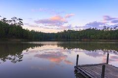 Houten dok op rustig meer met zonsondergang Stock Foto