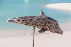 Houten dolfijn met duidelijk blauw water en wit zand als achtergrond royalty-vrije stock fotografie