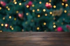 Houten donker tafelblad en vage Kerstmisboom bokeh Kerstmisachtergrond voor vertoning uw producten stock afbeeldingen