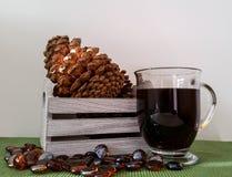 Houten doos met denneappels en mok zwarte koffie Stock Foto