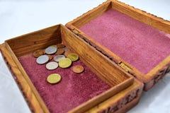Houten doos met rode tapijt en muntstukken Royalty-vrije Stock Fotografie