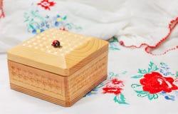 Houten doos voor juwelen op stof met borduurwerk Stock Fotografie