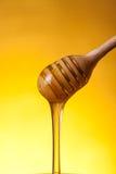 Houten drizzler en stromende honing stock afbeelding