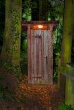 Houten droog toilethuis bij nacht in het bos Stock Afbeelding