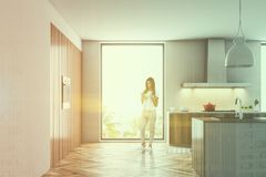 Houten en witte zolderkeuken met een kooktoestel, vrouw Royalty-vrije Stock Foto