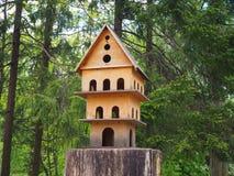 Houten gesneden vogelhuis met meerdere verdiepingen op een boomstomp, een voeder voor vogels in het park royalty-vrije stock foto