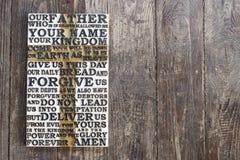 Houten gesneden woord van het Lord` s Gebed op de donkere sjofele houten plankachtergrond Stock Foto's