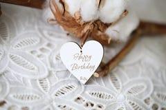 Houten gevormd hart met geschreven woorden Gelukkige Verjaardag op het, uitstekende doopvont stock afbeeldingen