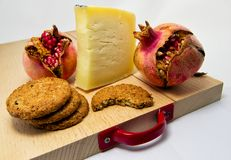 Houten hakbord met assortiment van kazen, koekjes en granaatappelfruit voor voedselconcept Stock Fotografie