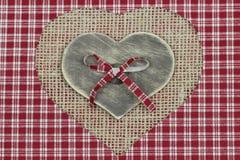 Houten hart op sjofele jute en plaidachtergrond Stock Fotografie