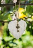 Houten hartdecor met een sleutel van het hart die op een boomtak hangen Wit hart leeg voor de naamtitel met een sleutel Royalty-vrije Stock Foto's