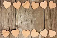 Houten harten die een dubbele grens vormen tegen rustiek hout Royalty-vrije Stock Foto's