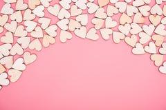 Houten harten op roze achtergrond met exemplaarruimte stock foto