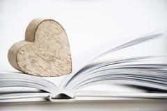 Houten hartvorm op een open boek Het concepten dichte omhooggaand van de liefdelezing Royalty-vrije Stock Foto's