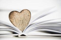 Houten hartvorm op een open boek Het concepten dichte omhooggaand van de liefdelezing Royalty-vrije Stock Afbeeldingen