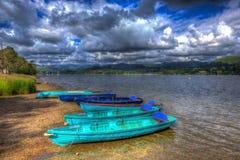 Houten het roeien boten door meer met bergen en blauwe hemel het Meerdistrict Cumbria Engeland het UK in HDR als het schilderen Royalty-vrije Stock Foto