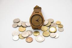 Houten horloge die op diverse stapel van het groottemuntstuk met terug wit zetten Stock Foto