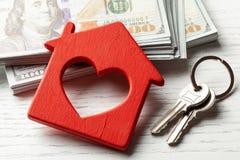 Houten hut met geld en sleutels op een witte achtergrond Het kopen of het huren of het verkopen Concept remont of verzekering voo royalty-vrije stock afbeelding